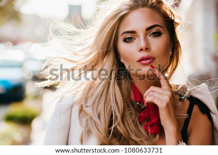 Sensual blue-eyed girl playfully posing on blur background touching lips with finger. Close-up portrait of magnificent blonde model in cute earrings with hair waving.