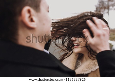 sensual bride with windy hair and groom embracing on road. happy couple hugging  and kissing in wind, romantic tender and sexual moment of emotional wedding couple