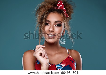 Shutterstock Sensual bright portrait of glamor elegant black woman model with curly hair in red dress posing on colorful background in studio