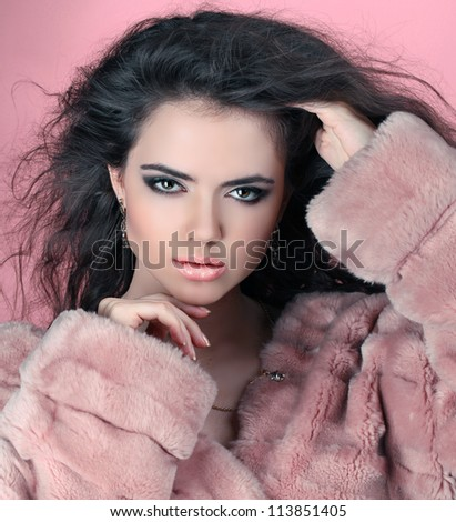 Sensual brunette woman in Luxury Fur Coat with shiny curly silky hair over pink