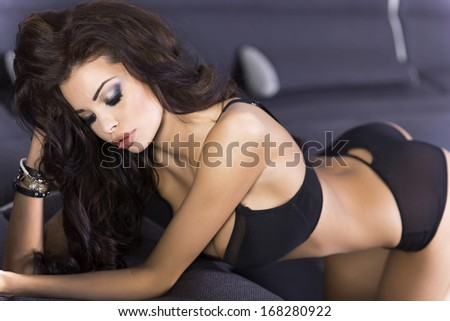 Stock Photo Sensual brunette woman posing in black sexy lingerie.