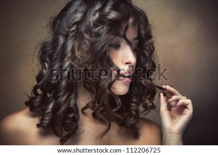 sensual brunette woman with shiny curly silky hair studio shot