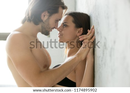 Sensual couple holding hands looking in the eyes leaning on wall, passionate lovers enjoy tender romantic moment in bedroom, man get closer admiring girlfriend almost kissing having sex foreplay