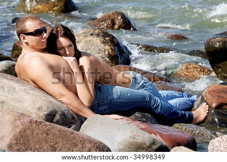 Sensual couple in jeans on a coastline