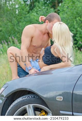 Sensual couple making love on the car\'s hood.