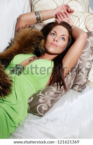 Sensual elegant young lady in green dress on the sofa