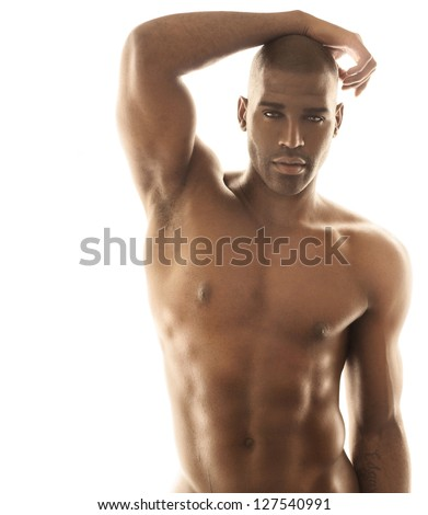 Sensual fashion portrait of a fit nude male model posing against bright white background