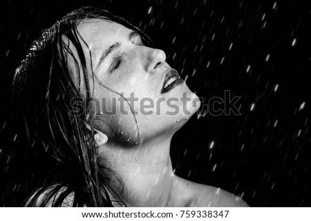 Stock Photo sensual girl under splash of water with fresh skin on black background, monochrome