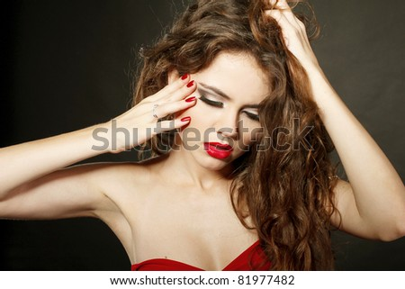 Sensual lady with red lips and red nails, touching face