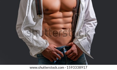 Sensual man. Muscular sexy man with torso. Sensual man with open white shirt. Handsome sexual strong man with muscular body in jeans with shirt on shoulder. Sensual concept