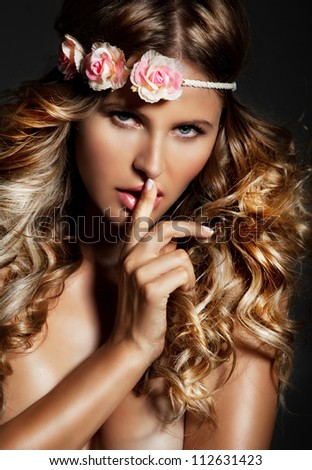 Sensual, natural  blond woman with flower on her head and long shiny, curly blond hair . Studio