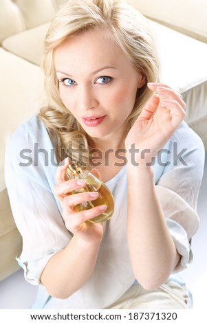 Sensual perfume - woman test perfume on her wrist .Form of a beautiful blonde holding in his hand a bottle of perfume