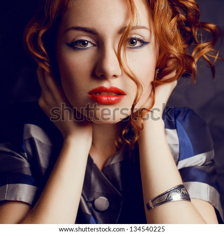 Sensual portrait of a beautiful young red-haired model in trendy jacket. Silver wristband on hand. Close-up. Perfect hair, skin and make-up. Studio shot