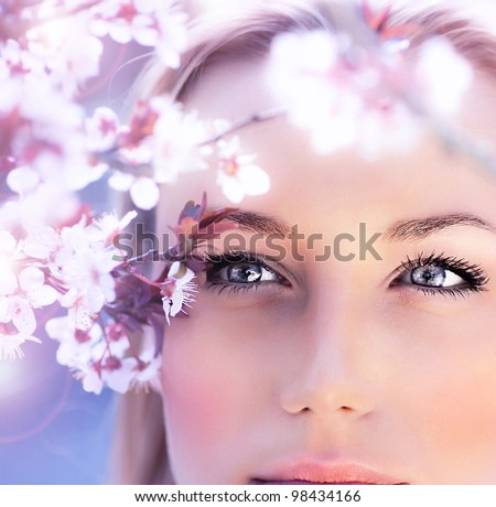 Sensual portrait of a spring woman, beautiful face, close up on blue eyes, female enjoying cherry blossom, dreamy girl with pink fresh flowers outdoor, seasonal nature, tree branch and natural beauty