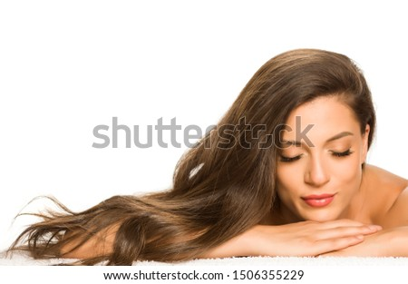 Sensual portrait of a young beautiful woman with long hair, lying on a white background