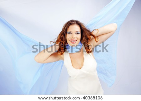 Sensual portrait of beautiful woman with flying blue scarf on white studio background
