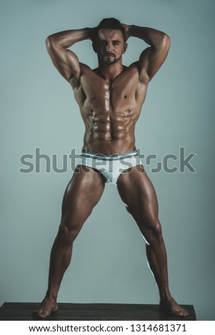 Sensual portrait of muscular male model in white modern underwear on grey background. Sport concept. Close up of muscular young male in underwear. Seductive man.