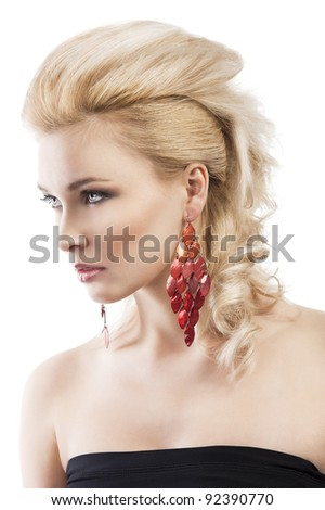 sensual portrait of very attractive blond woman with creative hair style and big fashion red earring with black top, she is turned three quarters and looks in front of her