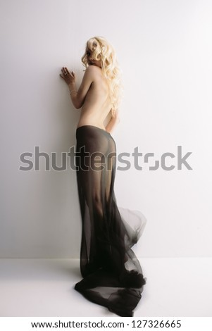 Sensual portrait of young attractive blond with transparent cloth over wall