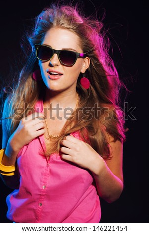 870a52a8c57 Sensual retro 80s fashion disco girl with long blonde hair and sunglasses.  Black background.