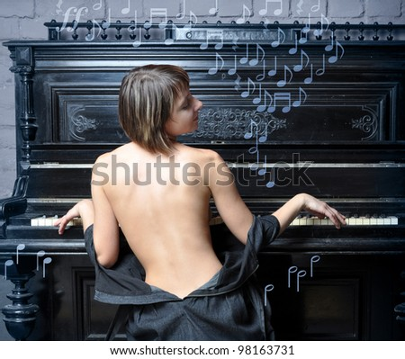 Sensual semi-dressed woman performing romantic music on piano, music symbols