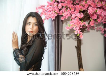 Sensual sexy dresses Asian women sensuality standing under pink flower tree near window.
