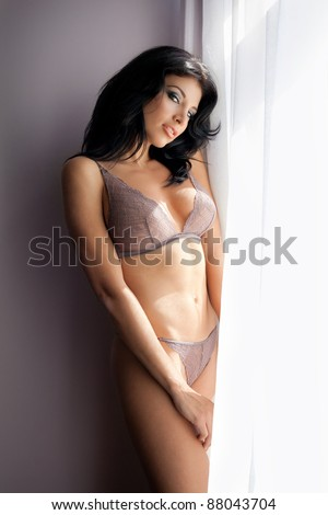 Sensual sexy woman posing in lingerie near bright window