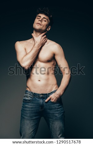 sensual shirtless man in jeans posing isolated on dark grey