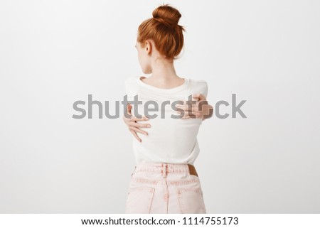 Sensual shot of attractive thin caucasian woman with natural red hair standing backwards to camera, hugging herself and turning head left, being upset with something, standing insecure over grey wall