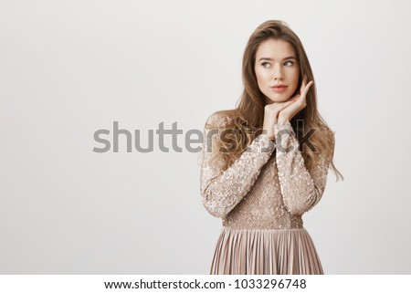 Sensual successful caucasian girlfriend leaning head on hands while standing in feminine pose in luxurious beige dress, looking aside with dreamy expression over gray background.
