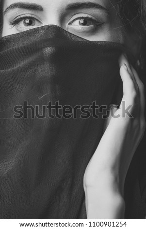 Sensual woman body. sensual woman with big eyes holding with hand very thin cobwed fabric black color looking forward closeup, vertical picture #1100901254