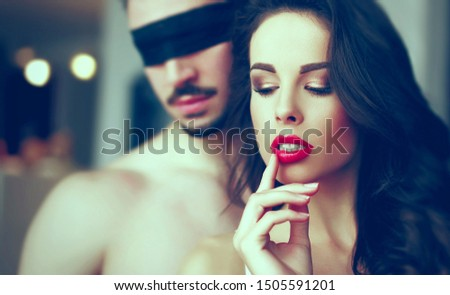 Sensual woman foreplay with young man in blindfold, desire