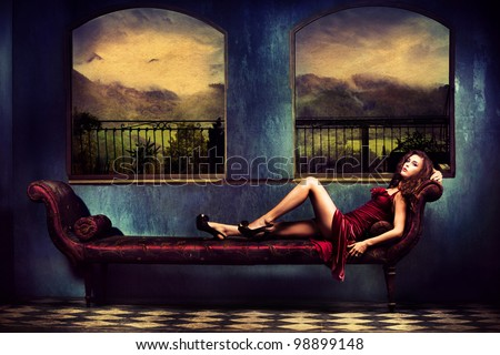 sensual woman in red dress lie on sofa in room with a view on mountains with rainy clouds