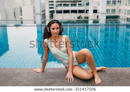 Sensual woman portrait wearing swimsuit and listening to music with headphones in swimming pool in Bangkok, Thailand. Filtered image.