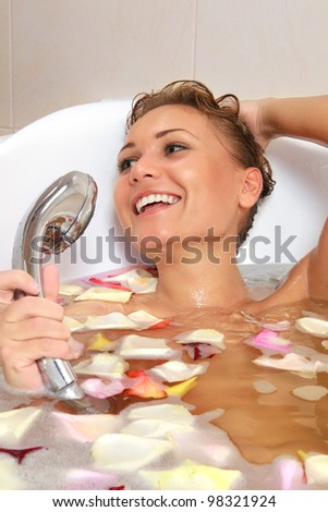 Sensual woman relaxing in bathtub with foam soap sud and rose petal