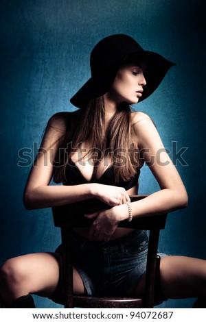 sensual woman with black hat posing on chair, studio shot