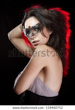 Sensual woman with bracelets of gold and silver, venetian mask with red light