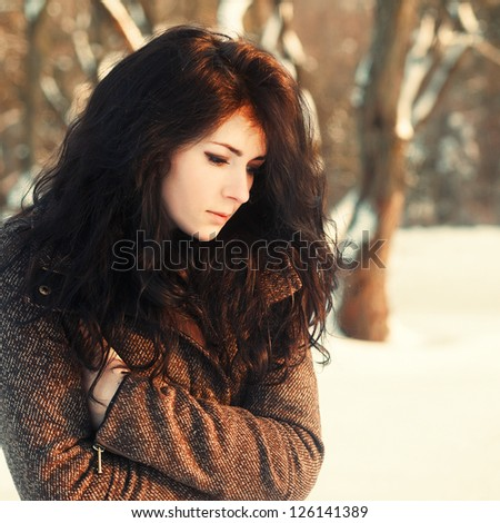 Sensual young brunette posing in winter park. Pretty young woman posing outdoor in warm coat.