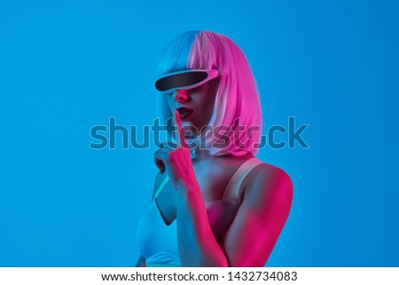 Sensual young lady in wig and futuristic digital goggles keeping finger near mouth and asking to keep silence against blue background