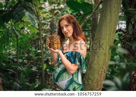 f2719efa3899f Sensual young redhead woman in a floral swimsuit with bare shoulders  holding a pineapple in hands