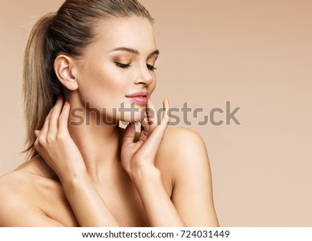 Sensual young woman enjoying her fresh clean skin. Portrait of beautiful woman of european appearance on beige background. Skin care and beauty concept #724031449