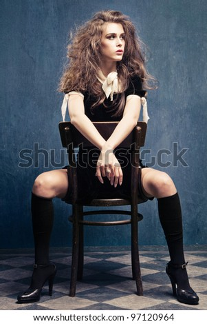 sensual young woman  in black dress, leggings and high heels sit on chair in grunge room with tiled floor