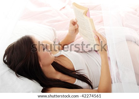 Sensual young woman laying in pink bed. Reading