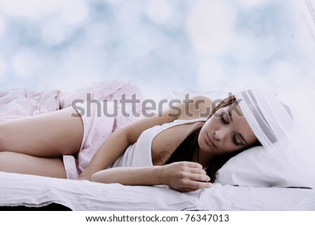 Sensual young woman laying in pink bed. Sleeping