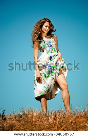 sensual young woman on summer field, blue sky in background, summer day