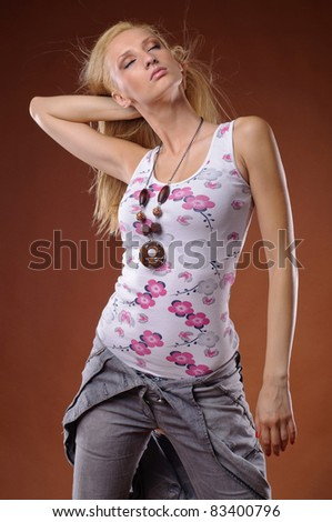 Sensual young woman posing in studio on brown background