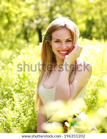Sensual young woman, smiles sweetly in the flowered garden,  day dreaming