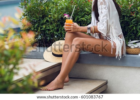 Sensual  young  woman with perfect slim tan legs  relaxing  with tasty fresh  orange juice  in trendy boho  tropical outfit.Tropical vacation. Details. Healthy Lifestyle.