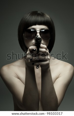 sensuality  beautifull  girl, to aim at target , with pistol, on dark background, glamour light