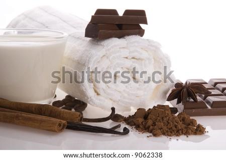 sensuality spa chocolate aromatherapy items - towel, milk, chocolate, anise stars, vanilla, cinnamon, cacao, coffee - stock photo